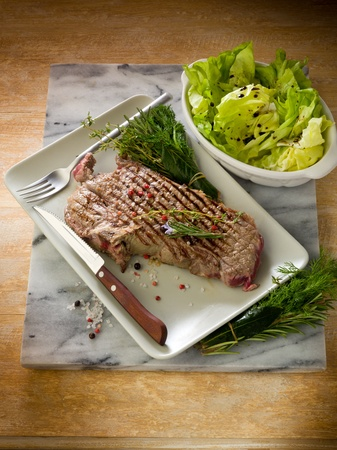 boned: grilled t-bone with green salad Stock Photo