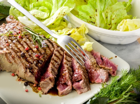 sliced steak with balsamic vinegar and green salad photo