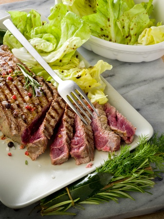 sliced steak with green salad photo