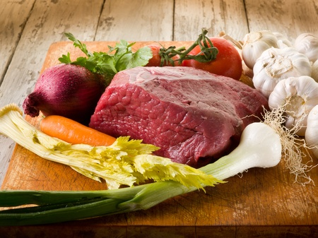 meat with vegetables ingredients over cutting board photo