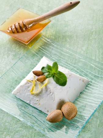 ricotta pudding with almond, honey and mint leaf photo