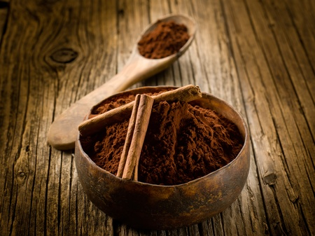 rich flavor: cacao powder with cinnamon on wood bowl