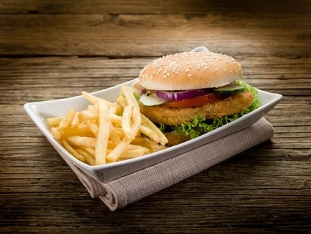sandwich de pollo: sándwich de hamburguesa con papas y ensalada de pollo Foto de archivo