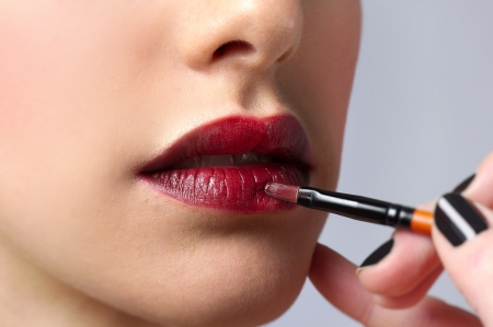 Applying lipstick with the paint-brush photo