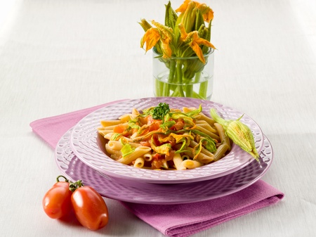 penne: pasta with zucchinis flower and fresh tomatoes,healthy food Stock Photo