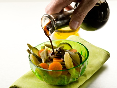 pouring balsamic vinegar over steamed vegetables salad