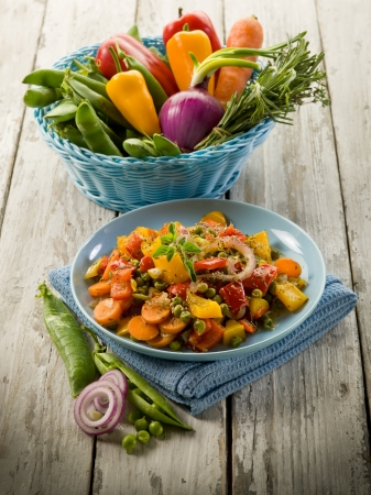 mixed sauteed vegetables on dish over wood background