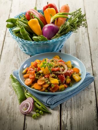 vegetable cook: verdure miste saltate in padella su un piatto su sfondo in legno Archivio Fotografico