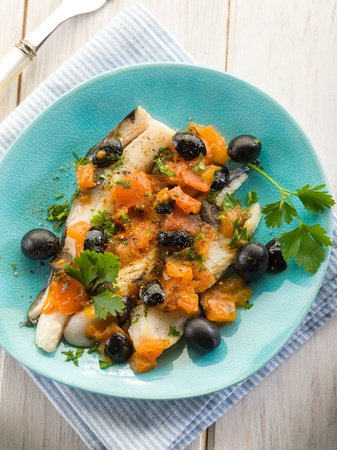 hake: cod fillet with black olives and fresh tomatoes Stock Photo