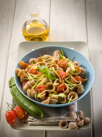 wheatmeal orecchiette with slice julienne zucchinis and fresh tomatoes photo