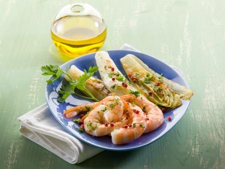 endivia: aperitivo con camarones a la parrilla y ensalada de escarola Foto de archivo