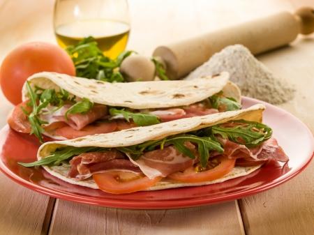 生ハム ルッコラとトマト、典型的なイタリア風サンドイッチのピアディーナ 写真素材