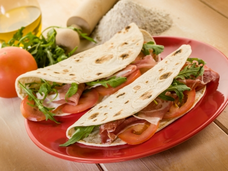 piadina with ham arugula and tomatoes, typical italian sandwich
