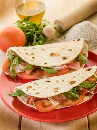 生ハム ルッコラとトマト、典型的なイタリア風サンドイッチ ピアディーナ 写真素材