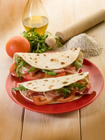 tortillas: piadina with ham arugula and tomatoes, typical italian sandwich