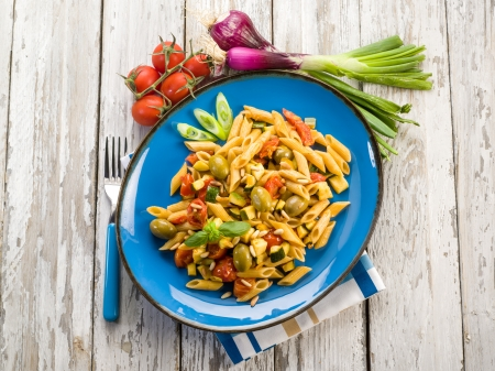pasta salad: cold pasta salad with pachino olives zucchins and pine kernel