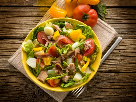 nicoise salad over wood background photo