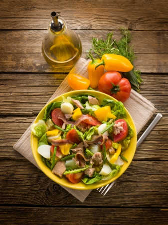 nicoise salad over wood background