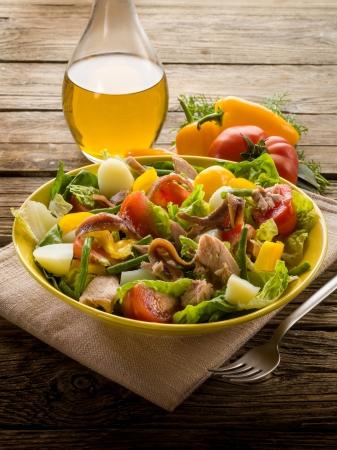 nicoise salad over wood background