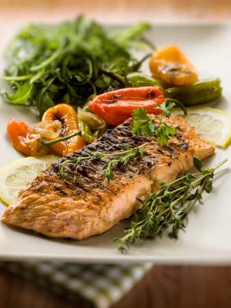 grilled salmon with capsicum and arugula, selective focus photo