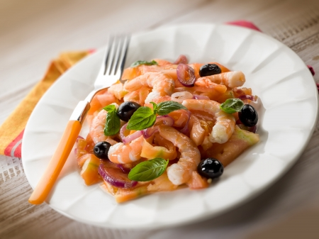 salad with shrimp tomatoes and black olives, selective focus photo