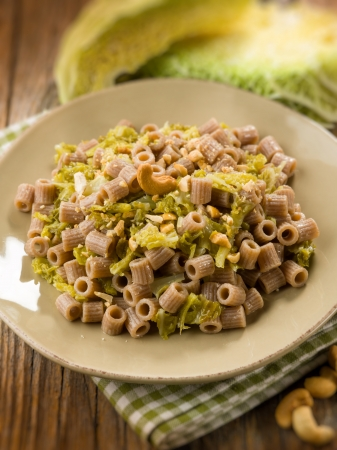 integral pasta with savoy cabbage and cashew nut, selective focus photo