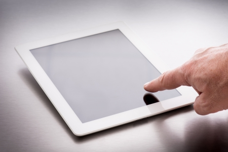 pointing finger on tablet pc over steel background photo