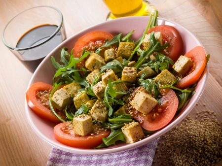 vegetarian food: salad with tofu tomatoes arugula and sesame seeds
