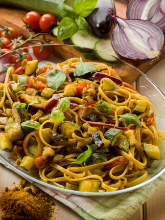 pasta with eggplants zucchinis tomatoes and curry photo