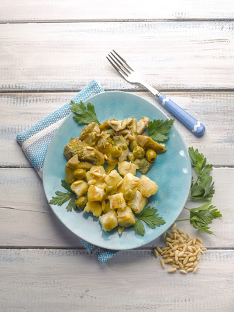 cod oil: stewed fish with artichoke olives and pine nuts Stock Photo