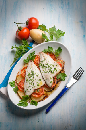 fish with potatoes and tomatoes photo