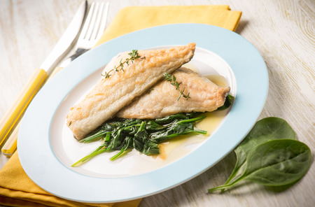 olive oil: fish fillet with fresh spinach