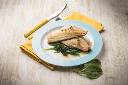 espinacas: filete de pescado con espinacas frescas Foto de archivo