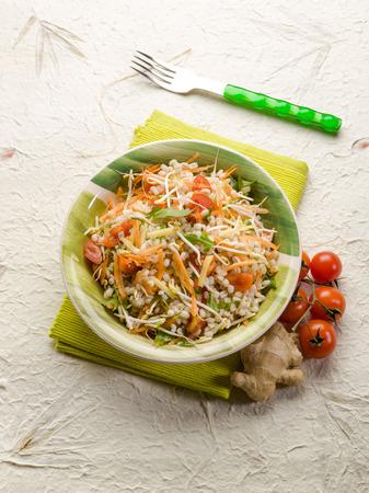 garnish: barley salad with ginger carrots arugula and tomatoes Stock Photo