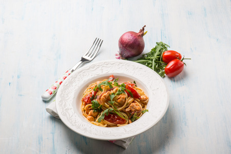 comida italiana: pasta with fresh salmon tomatoes and arugula Foto de archivo