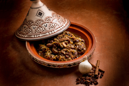 moroccan cuisine: tajine with meat, onion, dried grape and cinnamon