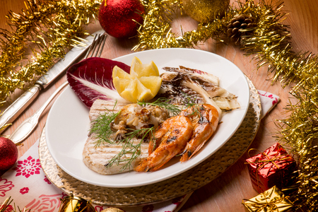 mixed grilled fish with red chicory over christmas table Stock Photo