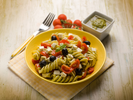 pasta salad with pesto feta tomatoes and black olives,  selective focus