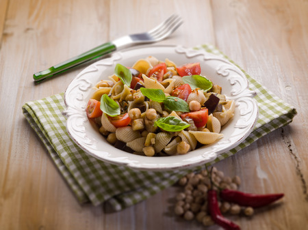 cold pasta salad with aubergine chickpeas and fresh tomatoes, selective focus