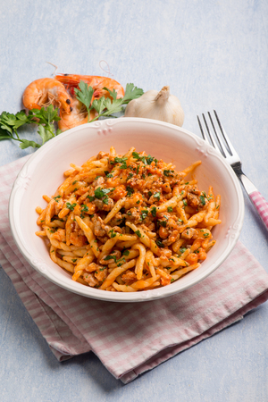 trofie pasta with shrimp tomatoes garlic and parsley Stock Photo