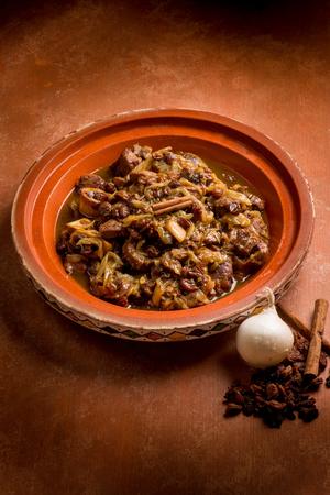 open tajine with meat, onion, dried grape and cinnamon