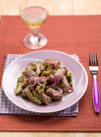 sausage with artichoke and onions , selective focus