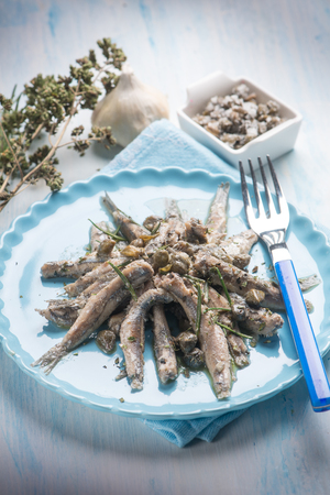 raw anchovies with capers herbs and olive oil, selective focus