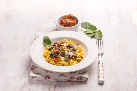 tagliatelle with fresh spinach gorgonzola cheese and dried tomatoes Stock Photo