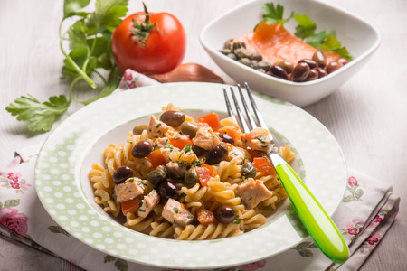 pasta with fresh salmon tomatoes capers and olives, selective focus