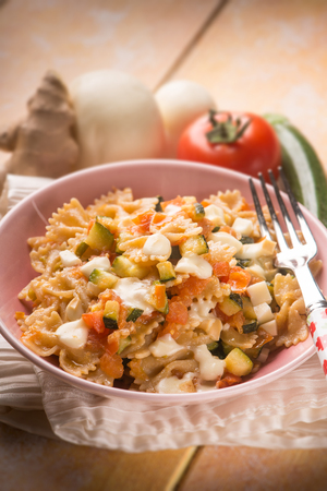 pasta with tomatoes zucchinis and scamorza cheese, selective focus Stock Photo