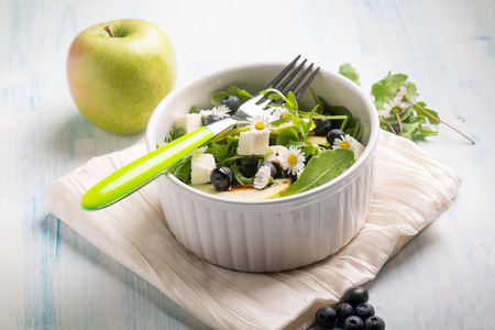 mixed salad with feta apple arugula blueberry and little daisy, selective focus Standard-Bild