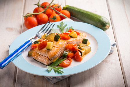 salmon with fresh tomatoes and zucchinis, selective focus Stock Photo