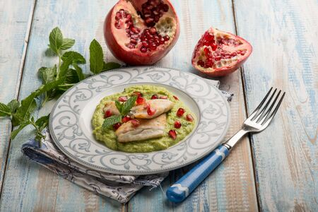 fillet fish over green peas cream with pomegranate