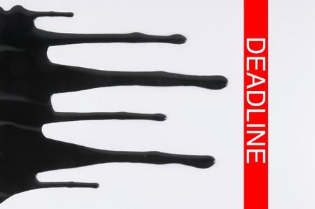 trailing: Black ink slowly trailing towards a red marking labeled DEADLINE. Horizontal shot. Stock Photo